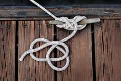 white rope securing boat to wooded dock