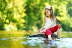 Cute little girl having fun by a river on warm summer day