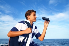 boy teenager binoculars explorer in blue beach